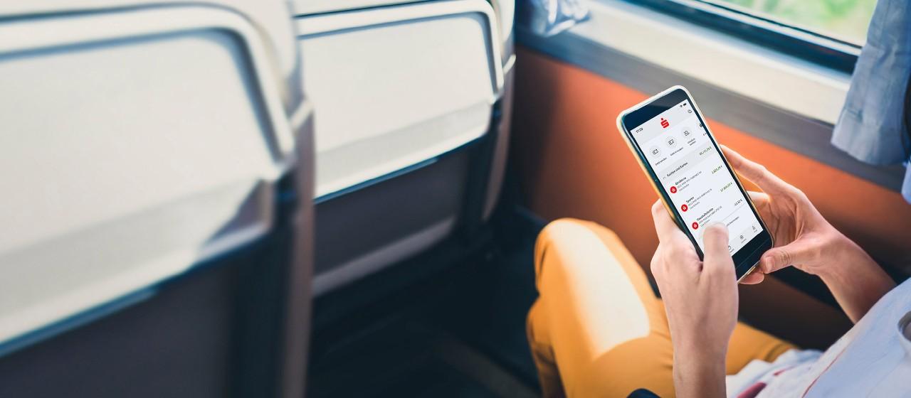junge Frau fotografiert mit Handy Überweisungsformular